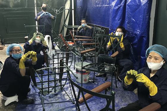 """F&B employees of the Sofitel Legend Metropole Hanoi in Vietnam repair furniture for the engineering department. (They are making the Accor """"Heartist"""" symbol for the camera.)   Photo courtesy of the hotel"""